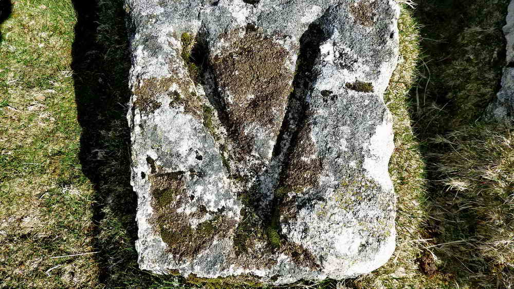 Close-up of a V stone, showing holes drilled at the ends of the arms